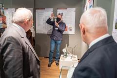 Pracownik prezentuje dwa paski papieru, goście obserwują isłuchają przemówienia