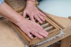 Dłonie dociskają sito zpulpą