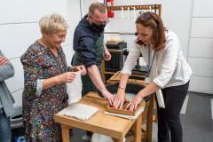 Jedna kobieta zpomocą instruktora dociska sito zpulpą, druga trzyma wdłoniach tkaninę. Wtle stoją uczestniczki warsztatu.
